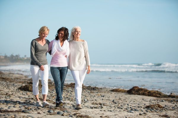 Three mature women are walking on a windy beach. The women embracing one another on a rocky, seaweed covered sandy beach. The ocean and clear blue skies are behind them. They are talking and enjoying a beautiful view.